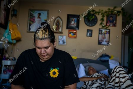 Sandy Vazquez, 30, left, cries as she sits on a fold out bed next to her mother Reyna Chautla, in their living room on Friday, June 11, 2021 in Los Angeles, CA. Sandy is recovering from foot surgery. Her mother recently had a stroke. Neither can move around their small home easily. She begins to tear up as she listens to her mother begin to cry. Sandy is transgender and her parents have been very supportive of her. (Francine Orr / Los Angeles Times)