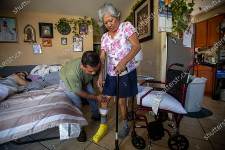 Jose Morales, left, rushes home after work to help his wife on Monday, June 21, 2021 in South Los Angeles, CA. Reyna had a stroke that paralyzed half her body. She needs a brace on her right foot to help her transition from the bed into the wheelchair. (Francine Orr / Los Angeles Times)