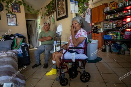 Jose Morales, left, sits next to his wife Reyna Chautla as she tears up Monday, June 21, 2021 in Los Angeles, CA. Reyna had a stroke that paralyzed half her body. She spends her day in bed until her husband arrives home and can help her out of bed. (Francine Orr / Los Angeles Times)