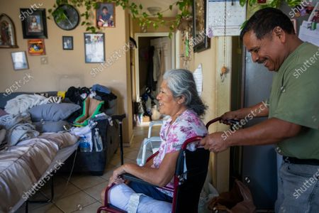 Stock Picture of Jose Morales, right, smiles as he helps his wife Reyna Chautla, left, to the dinner table Monday, June 21, 2021 in Los Angeles, CA. Jose cooked his family dinner after he arrived home from work. (Francine Orr / Los Angeles Times)
