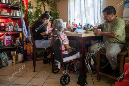 Sandy Vazquez, left, Reyna Chautla, middle, and Jose Morales, right, eat dinner together Monday, June 21, 2021 in Los Angeles, CA. Jose is cooking his family dinner because Sandy recently had foot surgery and his wife had a stroke. (Francine Orr / Los Angeles Times)