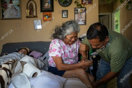 Jose Morales, right, rushes home after work to help his wife Reyna out of bed, June 21, 2021 in South Los Angeles, CA. Reyna had a stroke that paralyzed half her body. (Francine Orr / Los Angeles Times)
