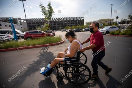 After work, Jose Morales guides his 30-year-old stepdaughter Sandy Vazquez in a wheelchair through a parking lot outside a wound care clinic in Willowbrook Wednesday, June 16, 2021 in Los Angeles, CA. (Francine Orr / Los Angeles Times)