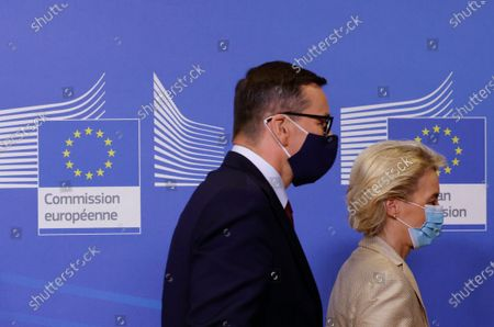 European Commission President Ursula von der Leyen, right, and Poland's Prime Minister Mateusz Morawiecki walk off the podium after an official greeting prior to a bilateral meeting at EU headquarters in Brussels