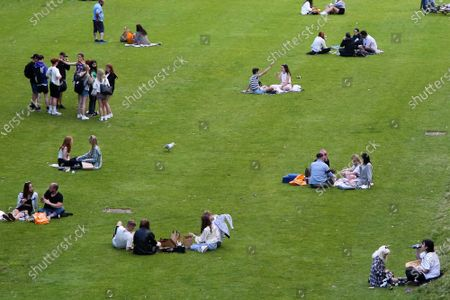 Edinburgh, Scotland, UK. People enjoy a warm evening in Princes Street Gardens in Edinburgh as warm weather continues in Scotland. According to the Met Office, a high of 22 degrees celsius is forecast for the rest of the week. Scotland's first minister, Nicola Sturgeon has said that Scotland will move to a 'modified' form of level 0 on 19 July and wearing of face coverings will remain mandatory.