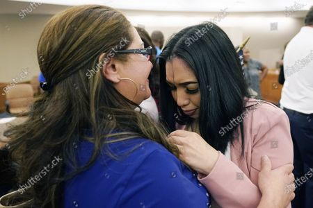 Stock Picture of Newly sworn in American citizen Michelle Gomez, right, overcome with emotion cries on her mother's shoulder following her naturalization ceremony at the United States Courthouse in Jackson, Miss., . Fourteen immigrants completed the requirements to become citizens including demonstrating a knowledge and understanding of U.S. history and government, demonstrating a loyalty to the principles of the U.S. Constitution, and taking the Oath of Allegiance