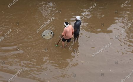 MCG workers trying to unclog a waterlogged stretch under Subhash Chowk Flyover during rain   on July 13, 2021 in Gurugram, India. After several false starts, the monsoon finally hit Delhi NCR on Tuesday. The first showers of monsoon caused waterlogging and massive traffic jams in different parts of the nation capital region causing snaking lines of vehicles on several busy road stretches, including at the Dhaula Kuan Ring Road, Barapullah and Kallindi Kunj flyovers.