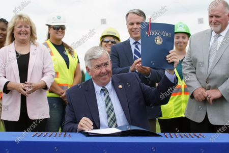 Missouri Governor Mike Parson holds up a copy of SB 262 that he has signed into law, during ceremonies in Hazelwood, Missouri on Tuesday, July 13, 2021. The legislation will increase transportation funding for critical state and local infrastructure projects across the state of Missouri. The funding will be raised from an increase in the state gas tax, which has not risen in over 20 years.