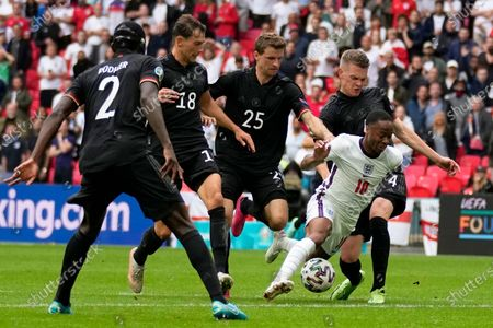 Germany's Matthias Ginter, right, tries to tackle England's Raheem Sterling during the Euro 2020 soccer championship round of 16 match between England and Germany at Wembley stadium in London