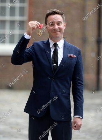 Stock Photo of Playwright James Graham shows his OBE for services to Drama and to Young People in British Theatre at St James's Palace London