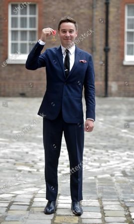 Stock Picture of Playwright James Graham shows his OBE for services to Drama and to Young People in British Theatre at St James's Palace London