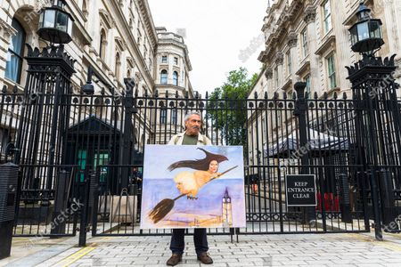 Political satire artist Kaya Mar stands outside Downing Street with his latest painting of British Prime Minister Boris Johnson on a broomstick ahead of Boris Johnson's departure from 10 Downing Street for Prime Minister Questions at parliament in London, Britain, 14 July 2021. Johnson faces the MPs' weekly question time in the House of Commons.
