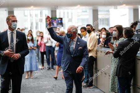Prince Charles waves good-bye next to Richard Gnodde, International CEO of Goldman Sachs, at the Goldman Sachs HQ in London
