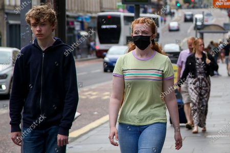 Stock Image of Edinburgh, Scotland, UK. A woman wearing a face covering in Edinburgh on a warm and sunny day. According to the Met Office, a high of 23 degrees celsius is forecast for the rest of the week. Scotland's first minister, Nicola Sturgeon has said that Scotland will move to a 'modified' form of level 0 on 19 July and wearing of face coverings will remain mandatory.