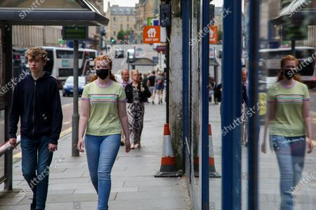 Edinburgh, Scotland, UK. A woman wearing a face covering in Edinburgh on a warm and sunny day. According to the Met Office, a high of 23 degrees celsius is forecast for the rest of the week. Scotland's first minister, Nicola Sturgeon has said that Scotland will move to a 'modified' form of level 0 on 19 July and wearing of face coverings will remain mandatory.