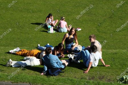 Stock Photo of Edinburgh, Scotland, UK. People enjoy a hot evening in Princes Street Gardens in Edinburgh as warm weather continues in Scotland. According to the Met Office, a high of 22 degrees celsius is forecast for the rest of the week. Scotland's first minister, Nicola Sturgeon has said that Scotland will move to a 'modified' form of level 0 on 19 July and 15 adults from 15 households can meet outdoors in a private garden or public place.