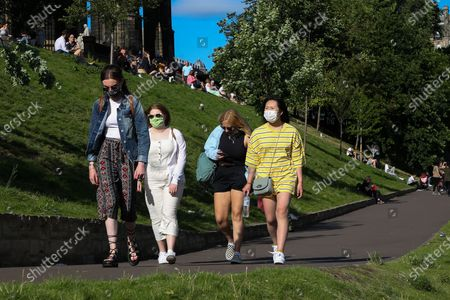 Edinburgh, Scotland, UK. Women wearing face coverings in Princes Street Gardens in Edinburgh as warm weather continues in Scotland. According to the Met Office, a high of 22 degrees celsius is forecast for the rest of the week. Scotland's first minister, Nicola Sturgeon has said that Scotland will move to a 'modified' form of level 0 on 19 July and 15 adults from 15 households can meet outdoors in a private garden or public place.