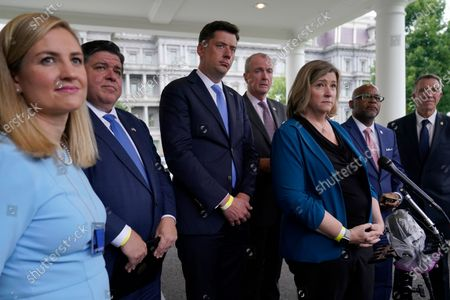 Mayors and governors, from left, Phoenix Mayor Kate Gallego, Illinois Gov. JB Pritzker, Oklahoma City Mayor David Holt, New Jersey Gov. Phil Murphy, Dayton (Ohio) Mayor Nan Whaley, Denver Mayor Michael Hancock and Vermont Gov. Phil Scott, listen as a reporter asks a question outside the West Wing of the White House in Washington, following their meeting with President Joe Biden to discuss the bipartisan infrastructure deal in the Senate