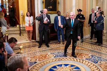U.S. Senator, Patrick Leahy (D-VT) taking a photo of the press as U.S. Senator, Jack Reed (D-RI) points at them as he walks near the Senate Chamber at the U.S. Capitol.