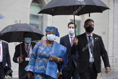 WTO Director-General Ngozi Okonjo-Iweala (C) wearing a protective face mask against the spread of the coronavirus disease (COVID-19) arrives for a Fisheries Subsidies Meeting of the WTO Trade Negotiations Committee at Ministerial Level, at the headquarters of the World Trade Organization (WTO) in Geneva, Switzerland, 15 July 2021. A virtual meeting of ministers takes place on the day to advance negotiations on curbing harmful fisheries subsidies.
