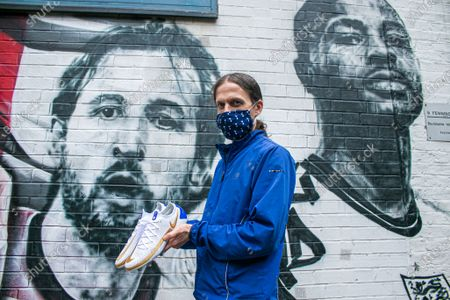 """Football fan Nick Herbert poses with the replica Harry Kane shoes he designed on Nike By You  in front of  the mural has been been unveiled  in Vinegar Yard near London Bridge by urban street artist MurWalls which was commissioned by London Mayor Sadiq Khan. The mural features an image of manager Gareth Southgate, Captain Harry Kane and Raheem Sterling """"You did us proud"""", and  celebrates the England football team's achievement in reaching the final of Euro Fooball Championship 2020"""