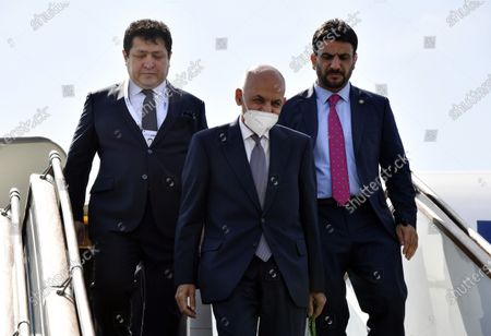 Afghan President Ashraf Ghani, center, flanked by his bodyguard and an official steps down from a plane upon his arrival at Tashkent International airport, Uzbekistan, . Uzbekistan's President Shavkat Mirziyoyev, Afghan President Ashraf Ghani and Pakistan's Prime Minister Imran Khan are among those expected to attend the conference along with foreign ministers of Central and South Asian nations, according to Mirziyoyev's official website