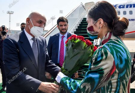Afghan President Ashraf Ghani, left, receives a bunch of flowers from a woman upon his arrival at Tashkent International airport, Uzbekistan, . Uzbekistan's President Shavkat Mirziyoyev, Afghan President Ashraf Ghani and Pakistan's Prime Minister Imran Khan are among those expected to attend the conference along with foreign ministers of Central and South Asian nations, according to Mirziyoyev's official website