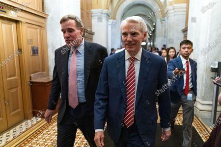 Sen. Mark Warner, D-Va., left, accompanied by Sen. Rob Portman, R-Ohio, walk for a closed door talks about infrastructure on Capitol Hill in Washington