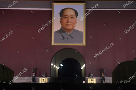 Chinese paramilitary policemen put on sunglasses while on duty, as spot lights light up Tiananmen Gate with its iconic portrait of late Chinese leader Mao Zedong in Beijing on