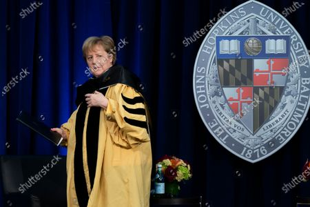 German Chancellor Angela Merkel walks back to her seat as she is awarded with a Doctor of Humane Letters, honoris causa, by John Hopkins University President Ronald Daniels at the Johns Hopkins School of Advanced International Studies campus in Washington