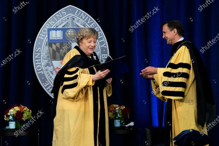 German Chancellor Angela Merkel is presented with her diploma as she is awarded with a Doctor of Humane Letters, honoris causa, by John Hopkins University President Ronald Daniels at the Johns Hopkins School of Advanced International Studies campus in Washington