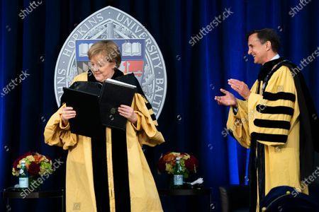 John Hopkins University President Ronald Daniels applauds as he presented German Chancellor Angela Merkel her diploma for Doctor of Humane Letters, honoris causa, at the Johns Hopkins School of Advanced International Studies campus in Washington
