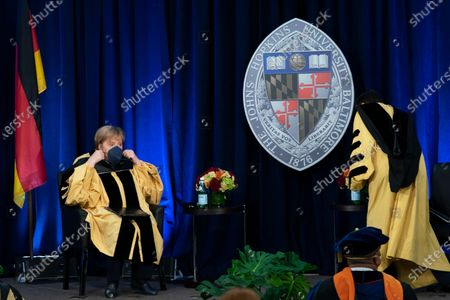 German Chancellor Angela Merkel puts her mask on as a ceremony awarding Merkel with a Doctor of Humane Letters, honoris causa, by John Hopkins University President Ronald Daniels at the Johns Hopkins School of Advanced International Studies campus in Washington
