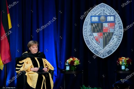 Stock Image of German Chancellor Angela Merkel listens during a ceremony awarding Merkel with a Doctor of Humane Letters, honoris causa, by John Hopkins University President Ronald Daniels at the Johns Hopkins School of Advanced International Studies campus in Washington
