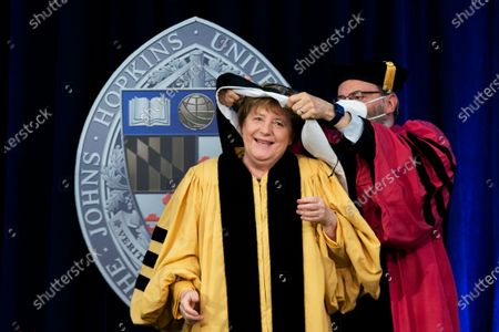 Stock Photo of German Chancellor Angela Merkel is assisted by John Hopkins University President Ronald Daniels with her hood as she is awarded with a Doctor of Humane Letters, honoris causa, at the Johns Hopkins School of Advanced International Studies campus in Washington