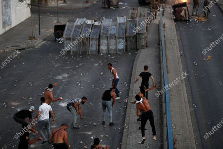 """Lebanese soldiers hide from stones behind their protective shield as they clash with supporters of Prime Minister-designate Saad Hariri who stepped down on Thursday in Beirut, Lebanon, . Hariri says he is stepping down, nine months after he was named to the post by the parliament. He is citing """"key differences"""" with the country's president, Michel Aoun"""