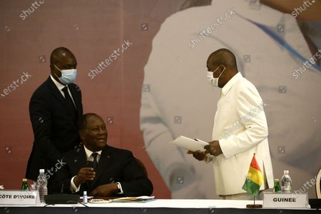 Ivorian President Alassane Ouattara (C) speaks with Guinean President Alpha Conde (R) during the summit of the International Development Association (IDA) in Abidjan, Ivory Coast, 15 July 2021. The event is attended by several African heads of state.