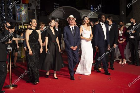 """Stock Picture of Lea Mysius, Celine Sciamma, Jehnny Beth, Lucie Zhang, Makita Samba, Jacques Audiard, Noemie Merlant and Valerie Schermann attend the """"Les Olympiades (Paris 13th District)"""" screening during the 74th annual Cannes Film Festival on July 14, 2021 in Cannes, France."""