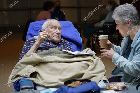This photo from, shows Barbara Goldstein, right, offering her 90-year-old father Melvin Goldstein a cup of coffee to go with his cookies as she visits him at the Hebrew Home at Riverdale in New York. Lawmakers are demanding that Gov. Andrew Cuomo lift remaining restrictions for visits at nursing homes. Some nursing homes are still only allowing people to visit loved ones for as little as 30 minutes a week