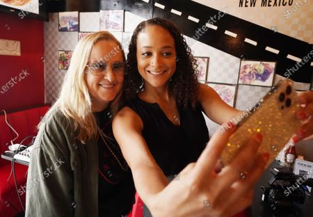 Singer Melissa Etheridge (L) takes a photograph with fan Pepper Baker at Cathy's Kitchen in Ferguson, Missouri on Friday, July 16, 2021. Etheridge, who is friends with owner Cathy Jenkins is having lunch at the small restaurant on the first day that the dining room is reopened. Cathy's Kitchen has been closed to the public for over a year due to the pandemic and became nationally known after protesters vandalized her business during the Michael Brown events of 2014.