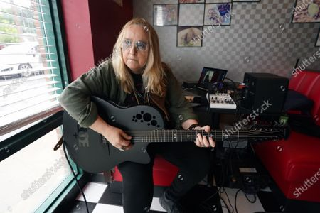 Stock Picture of Singer Melissa Etheridge tunes her guitar before having lunch at Cathy's Kitchen in Ferguson, Missouri on Friday, July 16, 2021. Etheridge, who is friends with Cathy Jenkins is having lunch at the small restaurant on the first day that the dining room is reopened. Cathy's Kitchen has been closed to the public for over a year due to the pandemic and became nationally known after protesters vandalized her business during the Michael Brown events of 2014.