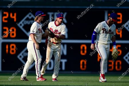 Philadelphia Phillies' Luke Williams, Travis Jankowski and Bryce Harper, from left, celebrate the team's 5-2 victory in the first baseball game of a doubleheader against the Miami Marlins, in Philadelphia