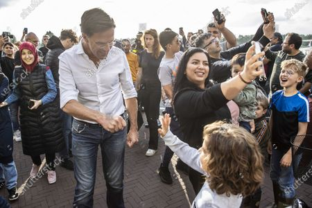 Dutch Prime Minister Mark Rutte high-fives with a child as he is surrounded by people taking selfies upon visiting the flooded areas in Venlo, the Netherlands, 16 July 2021. Heavy rainfall has led to floods in various parts of the Netherlands and central Europe