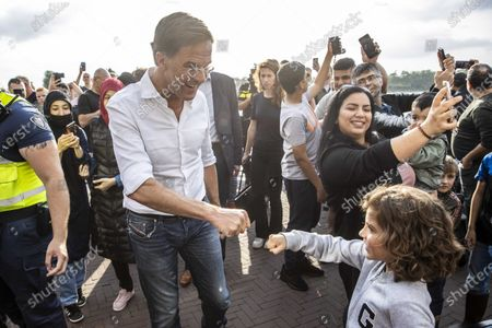 Dutch Prime Minister Mark Rutte fist-bumps with a child as he is surrounded by people taking selfies upon visiting the flooded areas in Venlo, the Netherlands, 16 July 2021. Heavy rainfall has led to floods in various parts of the Netherlands and central Europe