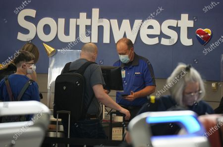 Southwest Airlines ticketing agent helps a traveller at the check-in counter at Denver International Airport in Denver. Sen. Maria Cantwell, D-Wash., who chairs the Senate Commerce Committee, sent letters Friday, July 16, 2021, to the CEOs of American, Southwest, Delta, JetBlue, Republic and Allegiant. She wrote that she is concerned by reports that have highlighted the role of worker shortages in a surge of delayed and canceled flights