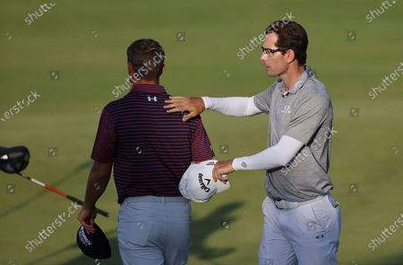 Stock Photo of South Africa's Dylan Frittelli pats United States' Jordan Spieth on the back after they completed their third round on the 18th green at the British Open Golf Championship at Royal St George's golf course Sandwich, England
