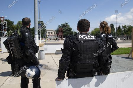Swiss riot police officers watch opponents to Cameroon's President Paul Biya who protest against his presence in Geneva, during a demonstration at Place des Nations in front of the European headquarters of the United Nation in Geneva, Switzerland, 17 July 2021.