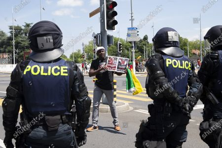 An opponent to Cameroon's President Paul Biya protests against Cameroon's President Paul Biya presence in Geneva in front of Swiss riot police, during a demonstration at Place des Nations in front of the European headquarters of the United Nation in Geneva, Switzerland, 17 July 2021.