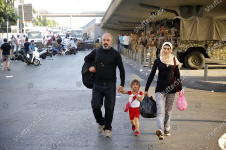 (210716) - BEIRUT, July 16, 2021 (Xinhua) - A family walk near the spot where protesters block a road in Beirut, Lebanon, on July 16, 2021. Lebanese Protestors closed roads in Beirut for the second day on Friday, a day after the resignation of Prime Minister-designate Saad Hariri. Hariri announced on Thursday his failure to form a cabinet, citing irreconcilable disagreements with President Michel Aoun. The announcement has prompted a dozen of protests across the country.
