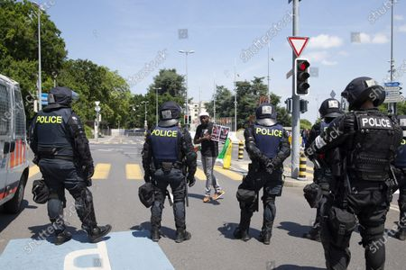 An opponent of Cameroon's President Paul Biya protest protests in front of Swiss riot police, at place des Nations in front of the European headquarters of the United Nation in Geneva, Switzerland, 17 July 2021.